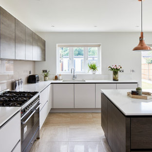 Inspiration for a large contemporary l-shaped open plan kitchen in London with flat-panel cabinets, grey cabinets, granite worktops, grey splashback, cement flooring, an island, beige floors and white worktops.
