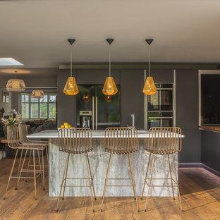 ロンドンの中サイズのコンテンポラリースタイルのおしゃれなキッチン (フラットパネル扉のキャビネット、グレーのキャビネット、木材カウンター、赤いキッチンパネル、レンガのキッチンパネル、シルバーの調理設備、無垢フローリング、茶色い床、白いキッチンカウンター) の写真