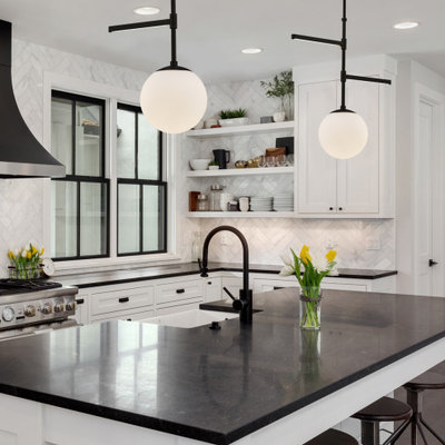 Example of a transitional l-shaped dark wood floor and brown floor kitchen design in Los Angeles with a farmhouse sink, shaker cabinets, white cabinets, white backsplash, stainless steel appliances, an island and black countertops