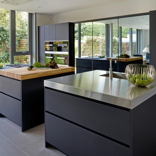 Design ideas for a contemporary galley kitchen in London with flat-panel cabinets, black cabinets, stainless steel worktops, stainless steel appliances and multiple islands.