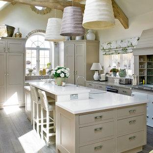 Ispirazione per una grande cucina ad U chiusa con ante lisce, ante beige, elettrodomestici in acciaio inossidabile, pavimento in legno massello medio e isola