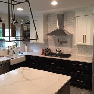 Inspiration för avskilda, stora moderna vitt u-kök, med en rustik diskho, luckor med infälld panel, svarta skåp, bänkskiva i kvartsit, vitt stänkskydd, stänkskydd i tunnelbanekakel, rostfria vitvaror, tegelgolv, en köksö och grått golv