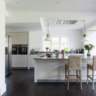 Design ideas for a large country single-wall kitchen in London with flat-panel cabinets, white cabinets, stainless steel appliances, dark hardwood flooring, an island, brown floors and grey worktops.