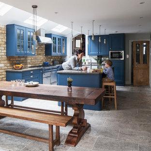 Cette image montre une cuisine américaine traditionnelle en L de taille moyenne avec un placard avec porte à panneau encastré, des portes de placard bleues, un plan de travail en granite, une crédence beige, une crédence en brique, un électroménager en acier inoxydable, un îlot central, un sol gris et un plan de travail gris.