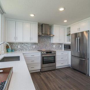 Foto di una cucina ad U chic con lavello sottopiano, ante in stile shaker, ante bianche, paraspruzzi a effetto metallico, elettrodomestici in acciaio inossidabile e parquet scuro
