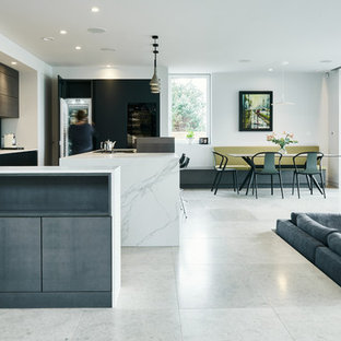 Photo of a contemporary open plan kitchen in Devon with a submerged sink, flat-panel cabinets, black cabinets, white splashback, integrated appliances, an island, white floors and white worktops.