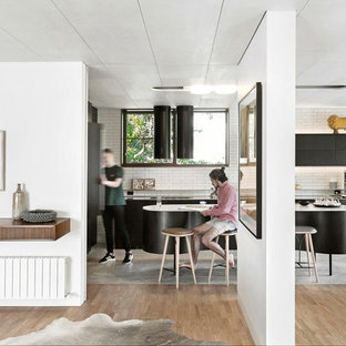 Photo of a large midcentury l-shaped open plan kitchen in Melbourne with white splashback, subway tile splashback, flat-panel cabinets, black cabinets, with island and grey floor.