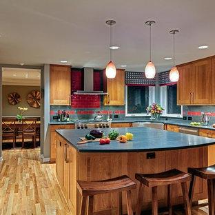 Выдающиеся фото от архитекторов и дизайнеров интерьера: большая п-образная кухня-гостиная в современном стиле с раковиной в стиле кантри, фасадами в стиле шейкер, фасадами цвета дерева среднего тона, столешницей из талькохлорита, красным фартуком, фартуком из керамической плитки, техникой из нержавеющей стали, светлым паркетным полом, островом, коричневым полом и синей столешницей