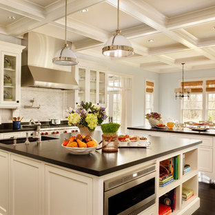 Large traditional eat-in kitchen inspiration - Eat-in kitchen - large traditional dark wood floor eat-in kitchen idea in Portland with stainless steel appliances, recessed-panel cabinets, white cabinets, white backsplash, subway tile backsplash, granite countertops, an undermount sink, two islands and black countertops