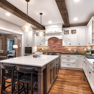 Large farmhouse eat-in kitchen ideas - Example of a large country l-shaped brown floor and painted wood floor eat-in kitchen design in New York with a farmhouse sink, beaded inset cabinets, white cabinets, granite countertops, brick backsplash, stainless steel appliances, an island, black countertops and red backsplash