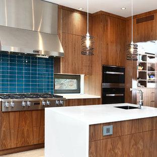 Пример оригинального дизайна: огромная угловая кухня в восточном стиле с обеденным столом, накладной раковиной, плоскими фасадами, светлыми деревянными фасадами, столешницей из кварцевого композита, синим фартуком, фартуком из стеклянной плитки, техникой из нержавеющей стали, полом из бамбука, двумя и более островами и серым полом