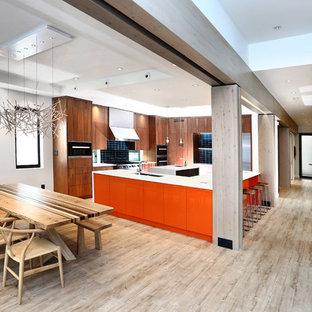 バンクーバーの巨大なアジアンスタイルのおしゃれなキッチン (ドロップインシンク、フラットパネル扉のキャビネット、淡色木目調キャビネット、クオーツストーンカウンター、青いキッチンパネル、ガラスタイルのキッチンパネル、シルバーの調理設備の、竹フローリング、グレーの床) の写真