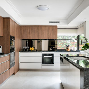 This is an example of a large contemporary l-shaped kitchen in Perth with an undermount sink, flat-panel cabinets, medium wood cabinets, black splashback, black appliances, with island, beige floor and black benchtop.