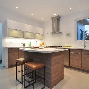 バンクーバーの中くらいのモダンスタイルのおしゃれなキッチン (アンダーカウンターシンク、フラットパネル扉のキャビネット、中間色木目調キャビネット、珪岩カウンター、ガラス板のキッチンパネル、シルバーの調理設備、コンクリートの床、白いキッチンカウンター、グレーの床) の写真
