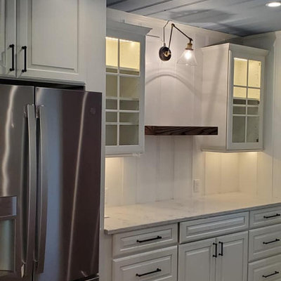 Example of a mid-sized farmhouse galley dark wood floor and brown floor eat-in kitchen design in Other with a farmhouse sink, shaker cabinets, white cabinets, quartz countertops, white backsplash, cement tile backsplash, stainless steel appliances and gray countertops
