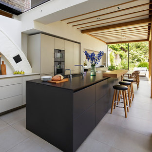 Inspiration for a contemporary galley kitchen in Cheshire with a submerged sink, flat-panel cabinets, grey cabinets, an island, grey floors and black worktops.