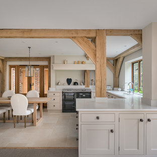 This is an example of a large rustic u-shaped open plan kitchen in Surrey with a submerged sink, recessed-panel cabinets, beige cabinets, granite worktops, beige splashback, integrated appliances, limestone flooring and no island.
