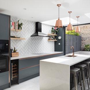 Einzeilige, Mittelgroße Moderne Wohnküche mit Unterbauwaschbecken, flächenbündigen Schrankfronten, blauen Schränken, Quarzit-Arbeitsplatte, Küchenrückwand in Weiß, Rückwand aus Metrofliesen, schwarzen Elektrogeräten, Kücheninsel, grauem Boden und weißer Arbeitsplatte in London