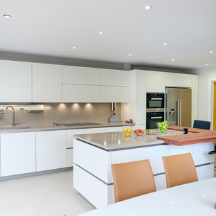 Inspiration for a mid-sized modern open plan kitchen in Surrey with flat-panel cabinets, white cabinets, limestone benchtops, stainless steel appliances, limestone floors, a peninsula, beige floor and beige benchtop.
