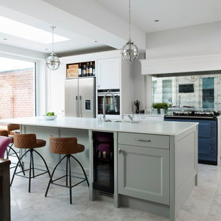 Photo of a mid-sized transitional eat-in kitchen in Belfast with with island, a double-bowl sink, recessed-panel cabinets, white cabinets, mirror splashback, coloured appliances and white floor.
