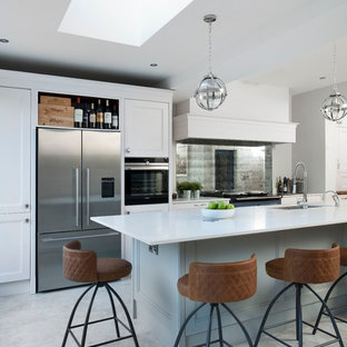 Photo of a medium sized traditional kitchen/diner in Belfast with a double-bowl sink, recessed-panel cabinets, white cabinets, mirror splashback, coloured appliances, an island and white floors.