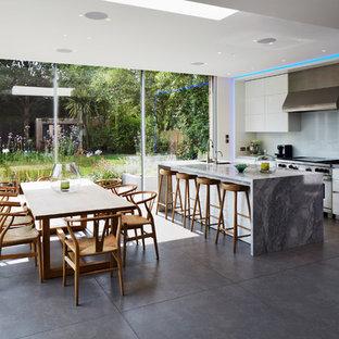 Exempel på ett modernt kök, med en undermonterad diskho, släta luckor, vita skåp, glaspanel som stänkskydd, rostfria vitvaror, en köksö och marmorbänkskiva