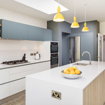 Example of a trendy l-shaped beige floor kitchen design in Other with an undermount sink, flat-panel cabinets, white cabinets, stainless steel appliances, an island and white countertops