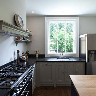 ロンドンの中サイズのヴィクトリアン調のおしゃれなキッチン (エプロンフロントシンク、シェーカースタイル扉のキャビネット、緑のキャビネット、御影石カウンター、黒い調理設備、濃色無垢フローリング、黒いキッチンパネル) の写真