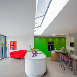 Inspiration for a contemporary u-shaped kitchen in Hertfordshire with flat-panel cabinets, green cabinets, stainless steel benchtops, panelled appliances, concrete floors, multiple islands and an undermount sink.
