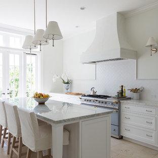 Пример оригинального дизайна: большая линейная кухня в классическом стиле с врезной раковиной, белыми фасадами, белым фартуком, цветной техникой, островом, обеденным столом, фасадами с утопленной филенкой, мраморной столешницей, фартуком из керамогранитной плитки, полом из известняка и бежевым полом