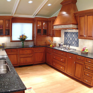 Inspiration for a large traditional u-shaped eat-in kitchen in Chicago with beaded inset cabinets, medium wood cabinets, granite benchtops, beige splashback, porcelain splashback, stainless steel appliances, a peninsula, black benchtop, a double-bowl sink, light hardwood floors and beige floor.