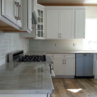 Eat-in kitchen - large coastal l-shaped eat-in kitchen idea in New York with a farmhouse sink, recessed-panel cabinets, white cabinets, gray backsplash, glass tile backsplash, stainless steel appliances and an island