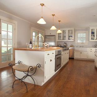 ニューヨークのトラディショナルスタイルのおしゃれなキッチン (エプロンフロントシンク、木材カウンター、シェーカースタイル扉のキャビネット、白いキャビネット、グレーのキッチンパネル、木材のキッチンパネル、シルバーの調理設備の、濃色無垢フローリング、ベージュのキッチンカウンター) の写真
