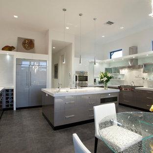 マイアミの大きいおしゃれなキッチン (ドロップインシンク、フラットパネル扉のキャビネット、グレーのキャビネット、クオーツストーンカウンター、白いキッチンパネル、シルバーの調理設備の、セラミックタイルの床、黒い床、白いキッチンカウンター) の写真