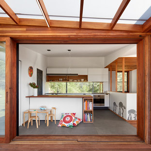 Design ideas for a midcentury kitchen in Wollongong with flat-panel cabinets, white cabinets, wood benchtops, window splashback, stainless steel appliances, concrete floors, a peninsula and grey floor.