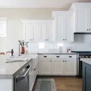 サンディエゴの大きいビーチスタイルのおしゃれなキッチン (エプロンフロントシンク、シェーカースタイル扉のキャビネット、白いキャビネット、クオーツストーンカウンター、白いキッチンパネル、サブウェイタイルのキッチンパネル、シルバーの調理設備の、クッションフロア、茶色い床、グレーのキッチンカウンター) の写真