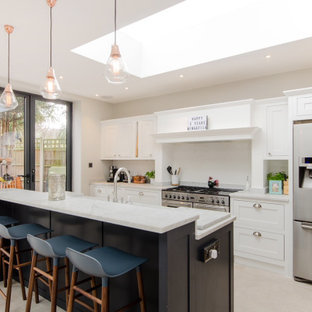 Photo of a classic galley kitchen/diner in London with shaker cabinets, white cabinets, white splashback, stainless steel appliances, an island, white floors and white worktops.