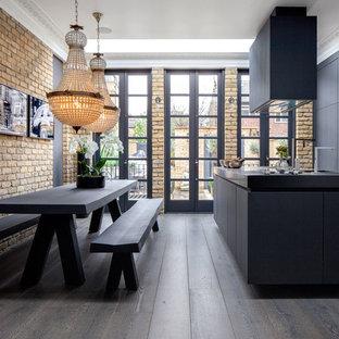 Esempio di una cucina industriale di medie dimensioni con ante lisce, ante nere, top in cemento, elettrodomestici da incasso, parquet scuro, isola e pavimento marrone