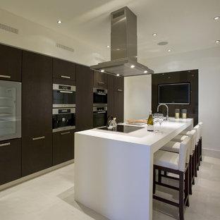 Immagine di un cucina con isola centrale moderno con elettrodomestici in acciaio inossidabile, pavimento in gres porcellanato, pavimento beige, ante lisce, ante in legno bruno e top in quarzo composito