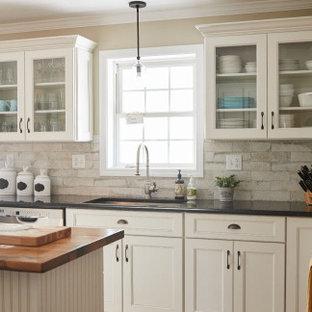 他の地域の中くらいのトランジショナルスタイルのおしゃれなキッチン (アンダーカウンターシンク、落し込みパネル扉のキャビネット、ベージュのキャビネット、クオーツストーンカウンター、マルチカラーのキッチンパネル、レンガのキッチンパネル、シルバーの調理設備、淡色無垢フローリング、黒いキッチンカウンター) の写真