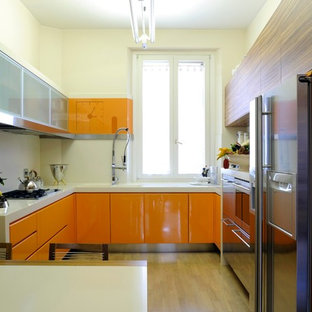 Mid-sized contemporary enclosed kitchen photos - Example of a mid-sized trendy u-shaped light wood floor enclosed kitchen design in Rome with flat-panel cabinets, orange cabinets, stainless steel appliances, solid surface countertops and white backsplash