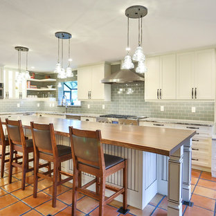 Ispirazione per una grande cucina chic con lavello a vasca singola, ante in stile shaker, ante gialle, top in legno, paraspruzzi verde, paraspruzzi con piastrelle di vetro, elettrodomestici bianchi, pavimento in travertino, isola e top marrone