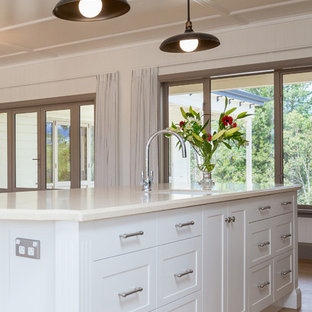 Photo of a large traditional u-shaped eat-in kitchen in Auckland with an undermount sink, recessed-panel cabinets, white cabinets, limestone benchtops, grey splashback, ceramic splashback, stainless steel appliances, laminate floors and with island.