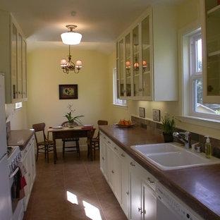 Idéer för små lantliga parallellkök, med en dubbel diskho, skåp i shakerstil, vita skåp, bänkskiva i betong, brunt stänkskydd, stänkskydd i skiffer, vita vitvaror, klinkergolv i porslin och brunt golv