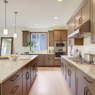 シアトルの中サイズのインダストリアルスタイルのおしゃれなキッチン (ダブルシンク、シェーカースタイル扉のキャビネット、茶色いキャビネット、クオーツストーンカウンター、白いキッチンパネル、セラミックタイルのキッチンパネル、シルバーの調理設備、クッションフロア) の写真