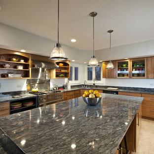 Bild på ett mellanstort funkis kök, med granitbänkskiva, en undermonterad diskho, släta luckor, skåp i mellenmörkt trä, rostfria vitvaror, linoleumgolv och en köksö