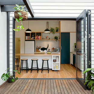 This is an example of a contemporary l-shaped kitchen in Melbourne with flat-panel cabinets, white cabinets, wood benchtops, white splashback, mosaic tile splashback, white appliances, medium hardwood floors, with island, brown floor and brown benchtop.