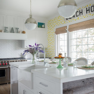 Beach style kitchen in New York with a farmhouse sink, shaker cabinets, white cabinets, white splashback, stainless steel appliances and with island.