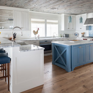 Inspiration for a coastal u-shaped medium tone wood floor and brown floor kitchen remodel in Bridgeport with a farmhouse sink, recessed-panel cabinets, white cabinets, blue backsplash, stainless steel appliances, an island and gray countertops