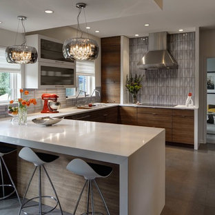 Design ideas for a retro kitchen in Chicago with flat-panel cabinets, medium wood cabinets, grey splashback, stainless steel appliances, grey floors and white worktops.